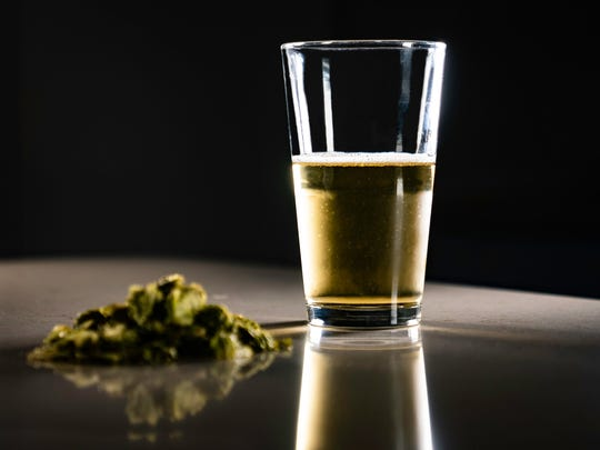 Legalizing recreational marijuana has become a heated topic in various states. Shown here is a cannabis and a half-full glass of beer.
