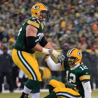Green Bay Packers right tackle Bryan Bulaga, left, helps quarterback Aaron Rodgers to his feet after being knocked down by the Atlanta Falcons last December.