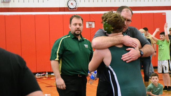 Wilson Memorial's Tom Branham gets a hug from Green Hornets head coach Chris Robinson after Branham won the 220-pound championship at the Shenandoah District Wrestling Tournament on Saturday, Feb. 3, 2018, at Stonewall Jackson High School in Quicksburg, Va.