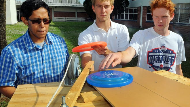 West Shore Jr./Sr. High second-year AP Physics students Talin Handa, Alex Heuser and John Nevins work on a gravity-powered Frisbee thrower project.
