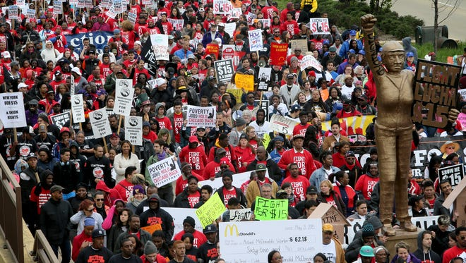 Thousands of activists and workers march near the McDonald's headquarters during a rally for pay of $15 an hour in Oak Brook, Ill., Wednesday, May 20, 2015.
