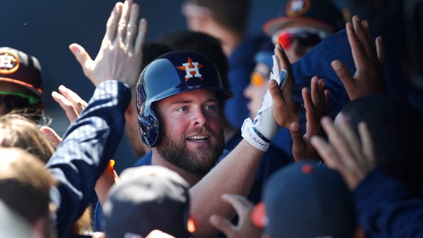 FILE - In this March 15, 2017, file photo, Houston Astros' Brian McCann celebrates in the dugout after hitting a home run in the first inning of a spring training baseball game against the Washington Nationals, in West Palm Beach, Fla. McCann was traded from the Yankees to the Astros. (AP Photo/John Bazemore, File)