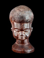This carving from Field Museum collections depicts scar tattooing, practiced in Tanzania and Mozambique. Tattooists make an incision with a small knife and then apply black pigment to the cut.