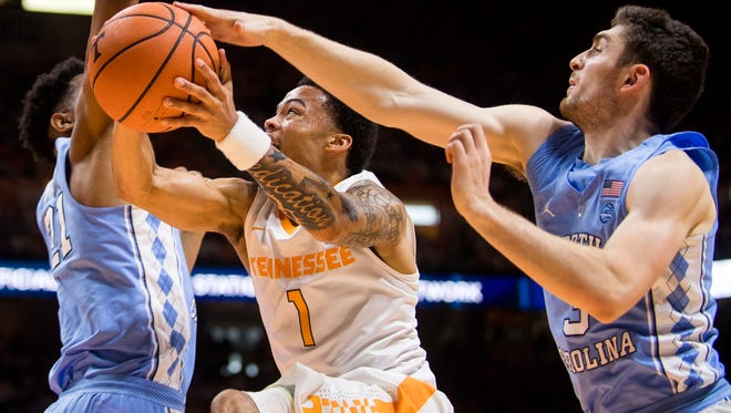 Tennessee guard Lamonte Turner (1) attempts a shot between North Carolina's Sterling Manley (21) and Andrew Platek (3) during Sunday's game.