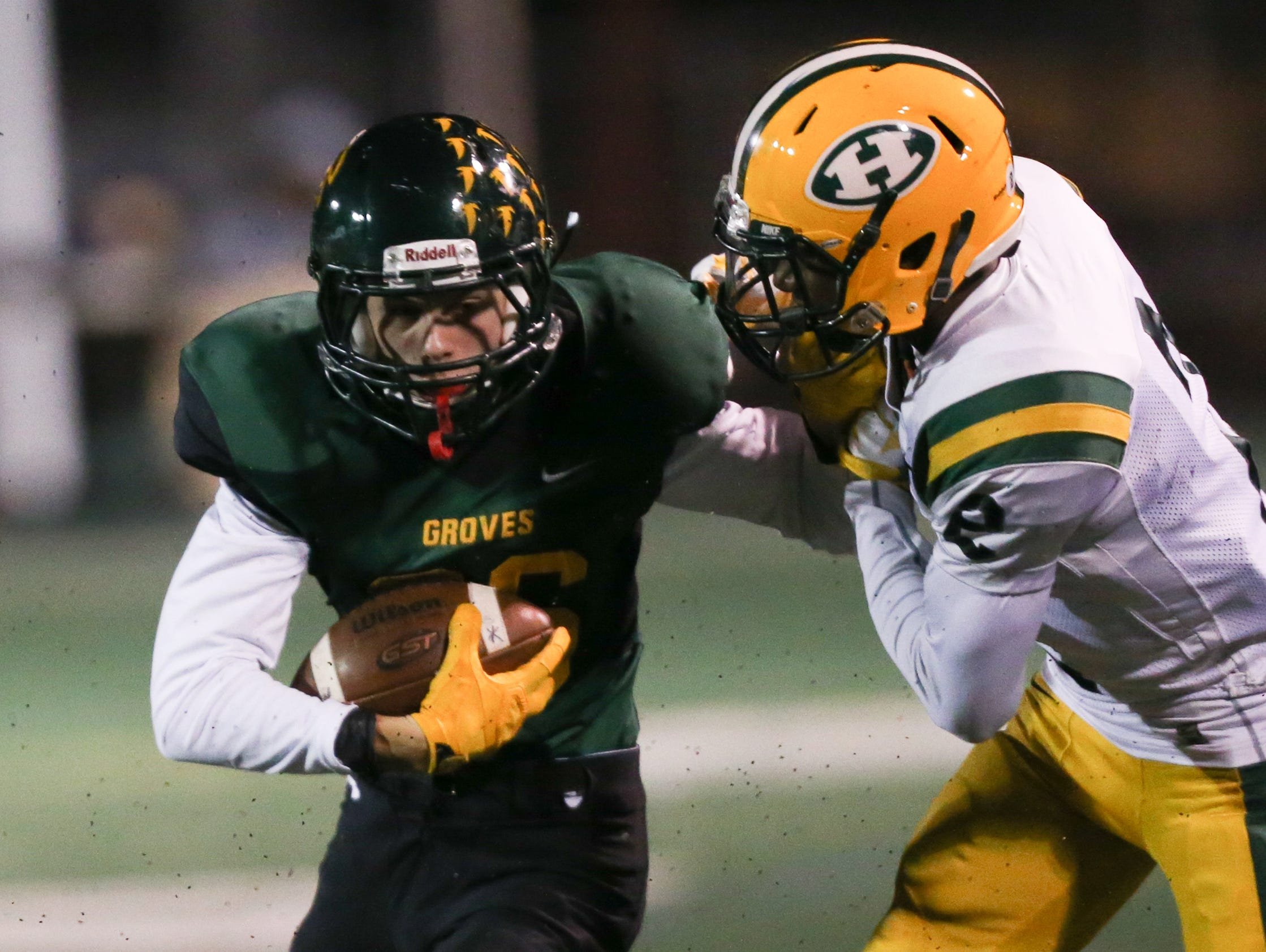 Birmingham Groves high school's Nate Higley is tackled by Farmington Hills Harrison's Kordell Agee during first-half action Friday, October 30, 2015 at Groves high school in Birmingham, Michigan.