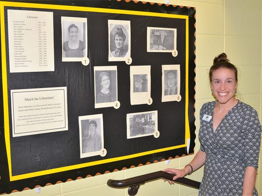 Farnsworth Public Library director Kristin Laufenberg poses next to a bulletin board activity where guests at the library's open house on June 28 could match names of former librarians with their picture.