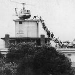 An Air America helicopter crew member helps people up a ladder on the roof of 18 Gia Long Street on April 29, 1975, in Saigon.
