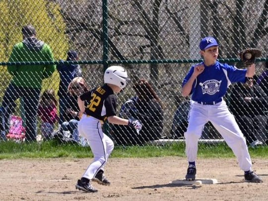 First baseman Nicholas Hoffman of the Major Division Royals looks to tag Pirates baserunner Tate Marco.