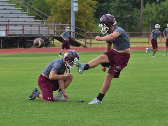 De Leon's Kevin Yeager boots an extra point from the hold of Jake Sanders during Tuesday's practice at De Leon.