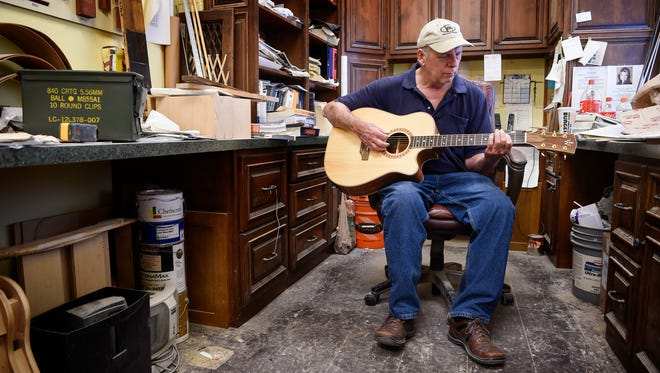 Woodworker Ed Wittenberg, who specializes in making cabinets and also makes guitars as a hobby, plays one of the guitars that he made in his shop in Triune, Tenn., Monday, Sept. 4, 2017.