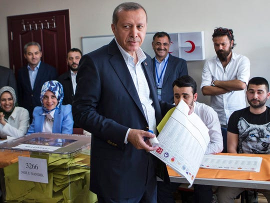 Turkish President, Recep Tayyip Erdogan (C), casts