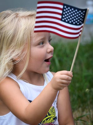 Ava Ashby, 3 years-old, waves a flag given to her during a visit from the Rolling Thunder veterans group at the Ark Crisis Care Center in Evansville Monday, July 3, 2017.