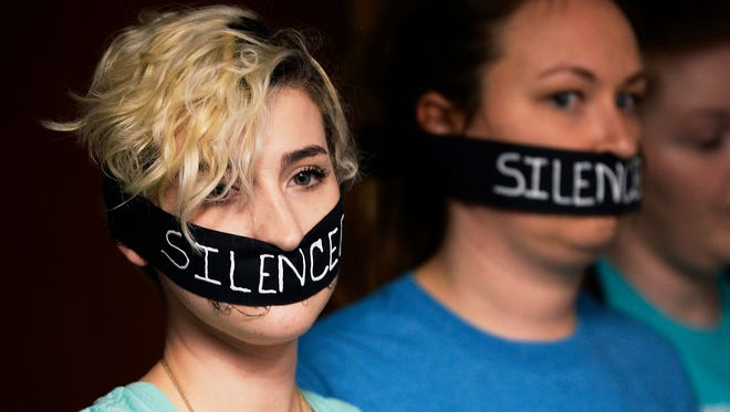 Survivors of sexual assaults by former MSU doctor Larry Nassar, Amanda Thomashow, left, 28, and Alex Neil-Sevier, 29, wear silence gags while listening to the Michigan State University Board of Trustees meeting, April 13, 2018, in East Lansing.