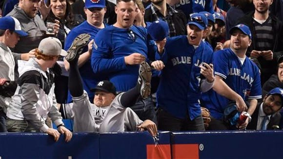 The Yankees' Brett Gardner falls into the stands after catching a foul ball April 14 in Toronto.
