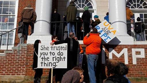 People gather with signs during a protest at the front porch of the Phi Kappa Psi fraternity house at the University of Virginia in Charlottesville on Saturday. The University of Virginia on Saturday suspended activities at all campus fraternal organizations amid an investigation into a published report in which a student described being sexually assaulted by seven men at a fraternity in 2012.