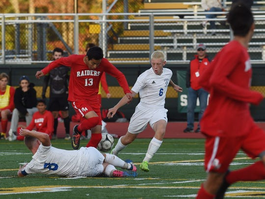 Red Hook's Jonathon Leon, left, struggles to move the ball forward during Saturday's Section 9 Class A boys soccer final against Goshen at Franklin D. Roosevelt High School.