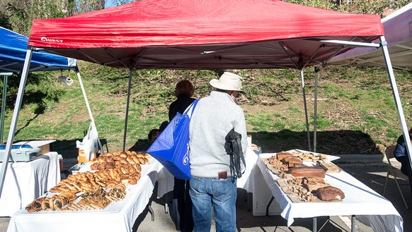 A shopper checks out the baked goods stand at Asheville