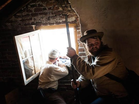 Confederate sharpshooters Ryan McCormick, left, of Smithsburg, Maryland, and Christopher Mattingly, of Taneytown, Maryland, take turns firing out of the attic window of the Shriver House in 2013.