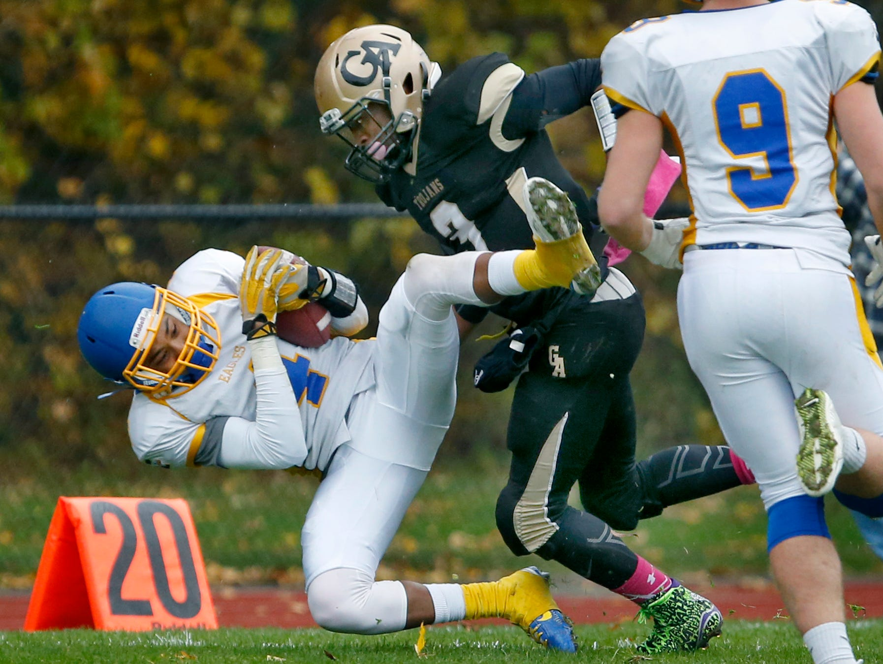 Irondequoit's Devyn Walker holds onto the ball while tackled by Greece Athena's Ta'Von Granison in the second quarter at Greece Athena High School.