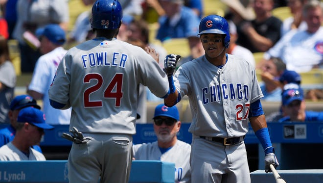 The Chicago Cubs' Dexter Fowler, left, is congratulated by Addison Russell after scoring on a single by Anthony Rizzo during the first inning against the Los Angeles Dodgers on Saturday, Aug. 27.
