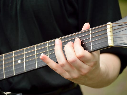 Closeup of guitar neck with guitarist playing