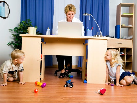 Woman working on computer while boy and girl play on floor around desk
