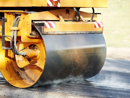 Bright yellow compactor roller at asphalting work