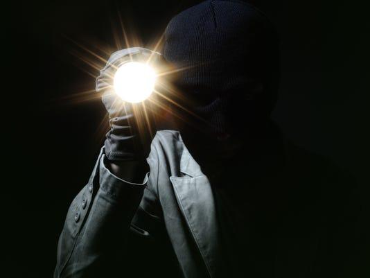 Thief holding a torch in dark