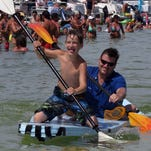 Father and son Jake and Mark Jenkins, 9, finish first in this heat of the Anything That Floats competition Sunday at off of Quietwater Beach as part of the Bamboo Willie's Jamaican Music Festival activities.