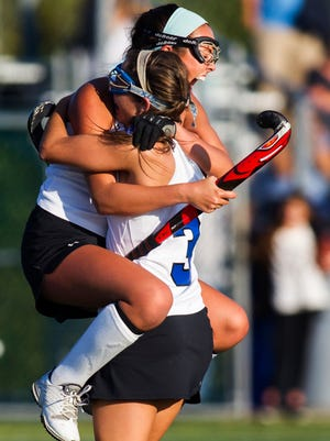 Middletown's Paige McKune leaps into the arms of teammate Brittany Bishop after Middletown's 4-2 win over Mount Pleasant at Middletown High School on Wednesday afternoon.