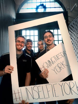 In this file photo, from right, Vince Moley, Rob Bruder, Benn Appleby and John VanSickle of Dataforma, Inc., pose for an unselfie during last year's #GivingTuesday. The national movement started in 2012 and encourages people to give back to their communities in the midst of the frenzied holiday shopping season. (Bil Bowden - For The York Dispatch)