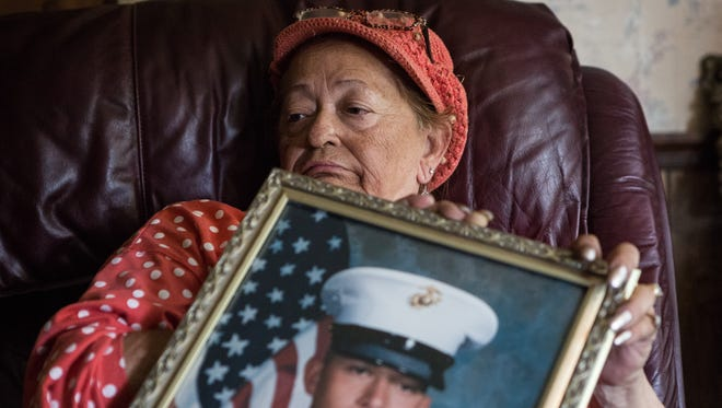 "Jeanne Cohee, of Mardela Springs, Maryland sits in her home holding a photo of her son Walter ""Trae"" III on Monday, May 22, 2017. The 26-year-old Marine died in Afghanistan while on a supply mission when an engine on his CH-53E Super Stallion helicopter failed and crashed into a mountain. Cohee was Maryland's first death from the war in Afghanistan."