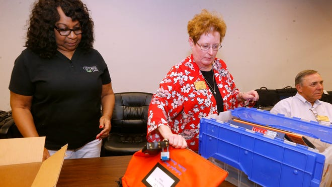 Carolyn Peebles, left and Felicia Hix unlock the election  ballots to be counted at the Rutherford County Election Commission on Election Day, Tuesday, May 1, 2018.