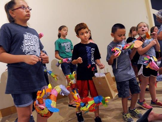 Children dangle their Quetzalcoatl puppets after a