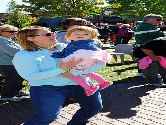 Farmington Hills resident Susan Dely dances with daughter Lucy at the Farmington Farmers Market .