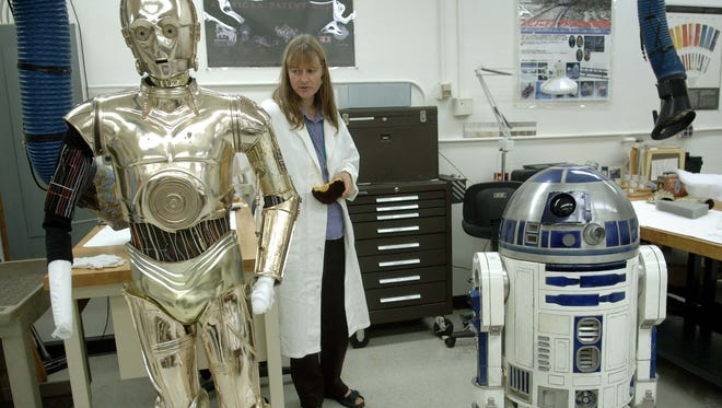 """Beth Richwine, Objects Conservator at the Smithsonian's National Museum of American History, explains how they are preparing C3PO, left, and R2D2 from """"Star Wars,"""" to be moved for temporary exhibition while the museum is closed."""