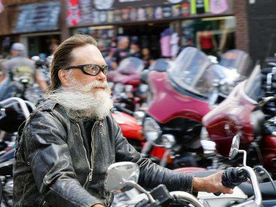 A rider's beard blows back in the wind as he cruises