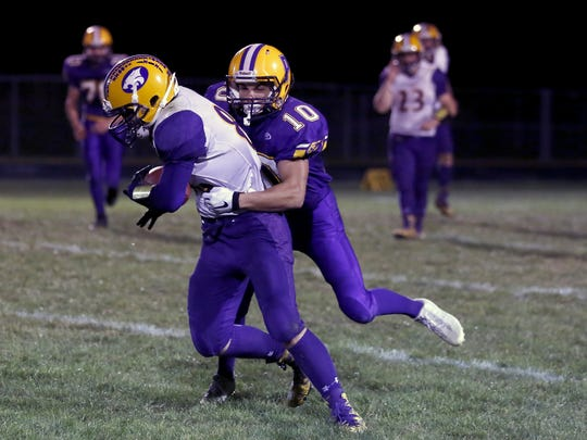 Pittsville's Bailey Herkert (10) tries to tackle Tommy Friday of Wild Rose with first place on the line in the Central Wisconsin Conference-Small.
