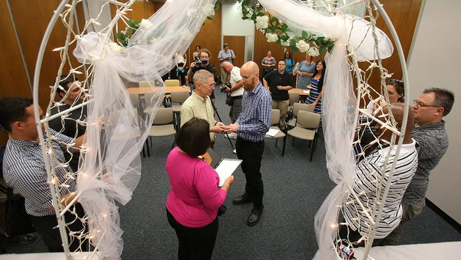 Bart Peterson, left, and Peter McNamara exchange wedding vows inside the City County Building in Indianapolis on Wednesday, June 25, 2014 — the day a federal judge ruled that Indiana's ban on gay marriage is unconstitutional. On Friday, June 27, 2014, an appeals court stopped the marriages pending an appeal of the federal judge's ruling.