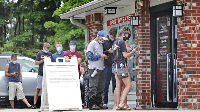 People line up at the Urgent Care clinic on Washington Street in Norwell to get the COVID19 rapid test. Many where in line at 7 a.m. on Thursday.