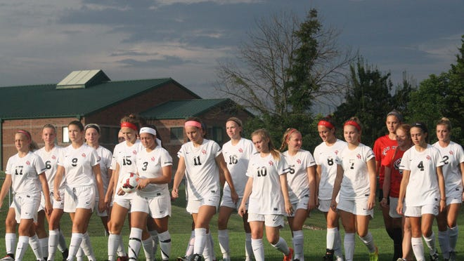 Oak Hills' girls soccer team walks across the field on Aug. 9 before a scrimmage against Loveland.