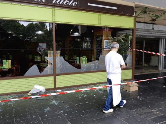 A man walks past a damaged restaurant in Les Flanades neighborhood of Sarcelles, France.