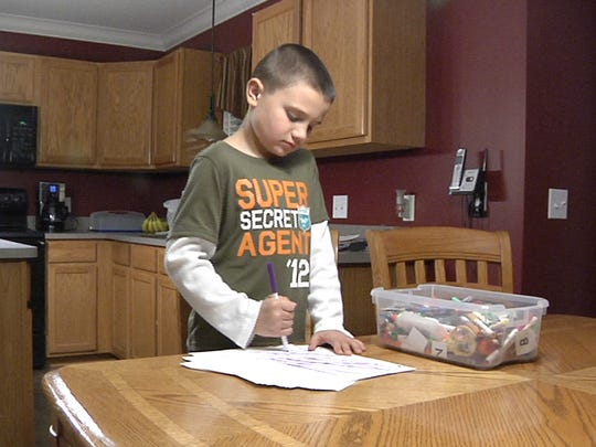 Blake Roberts, 10, uses a marker to color on a piece