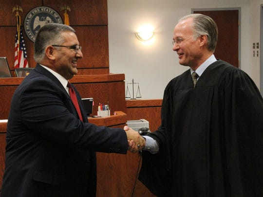Twelfth Judicial District Judge Jerry H. Ritter Jr., right, congratulates David Ceballes, left, after swearing in Ceballes as the new 12th Judicial District Attorney for Otero and Lincoln counties Monday.
