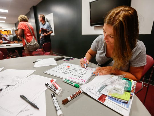 Renee Lembke, of Camdenton, MO., writes a message for her daughter, incoming freshman Karissa Lembke, during the college expo at Missouri State University on Tuesday, July 11, 2017.