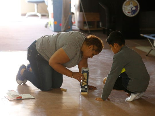 Victoria Snowden plays with one of her sons after she