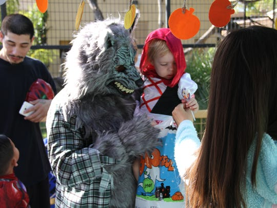 A little Red Ridding Hood gets a treat while her dad dressed as the Big Bad Wolf holds her during Alamogordo's Zoo Boo Saturday.