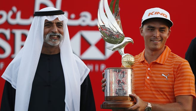 Rickie Fowler celebrates with his trophy after winning he Abu Dhabi Golf Championship in the  United Arab Emirates on Sunday.