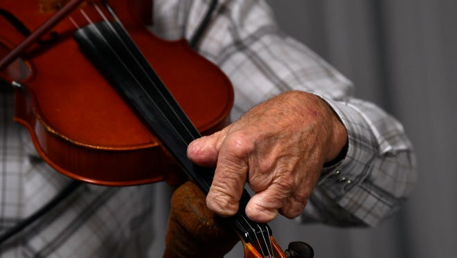 """""""Fingerless Fiddler"""" Roy Thackerson uses a special wooden support to prop his fiddle up Friday at the country musical at the Olden Community Center. Thackerson lost most of the fingers on his left hand in a childhood accident but learned how to play guitar as a young mane and then later, country fiddle."""