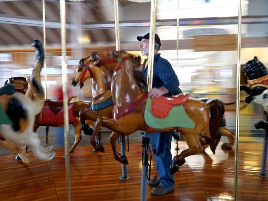 Todd Goings rides the carrousel and inspects each animal